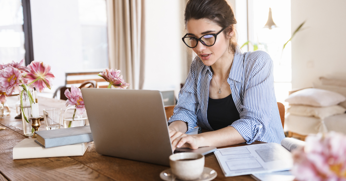 woman with glasses working on laptop